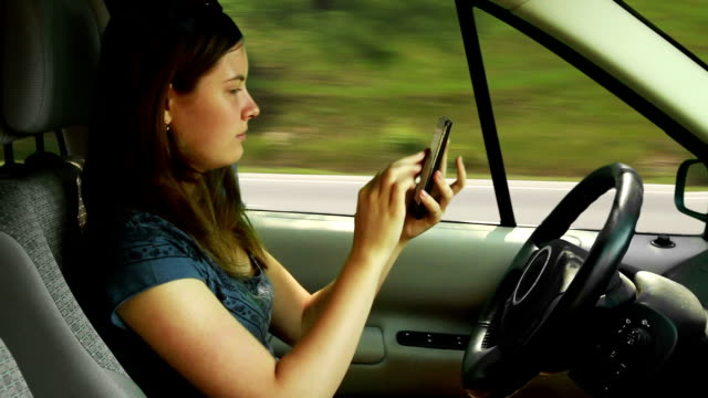 Teenager girl driving a car and playing with smart phone video
