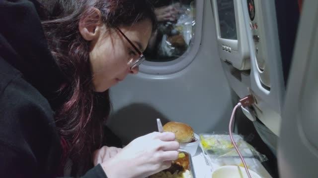 vídeos de stock, filmes e b-roll de adolescente menina come a bordo do voo internacional - 16 17 anos