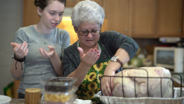 Teenager girl, granddaughter, and her grandmother, silver-haired senior woman, stuffing the turkey for a holiday dinner