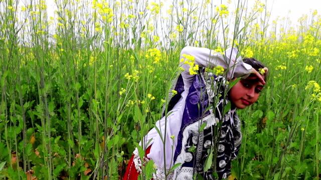 Tiener meisje verbergt zich achter de mosterd gewas plant video