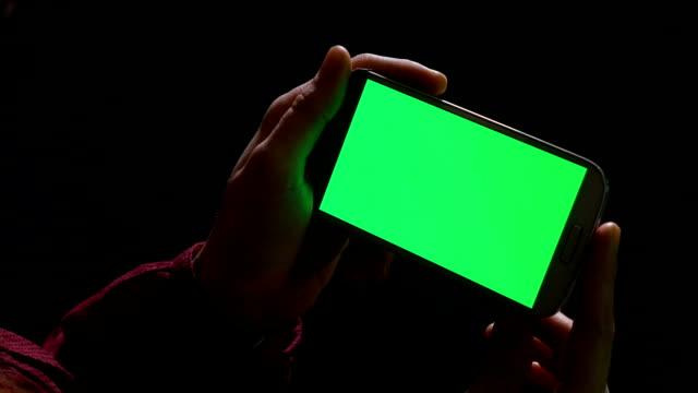 vidéos et rushes de fille d'adolescent retenant le téléphone intelligent dans des mains à l'intérieur dans l'obscurité - horizontal