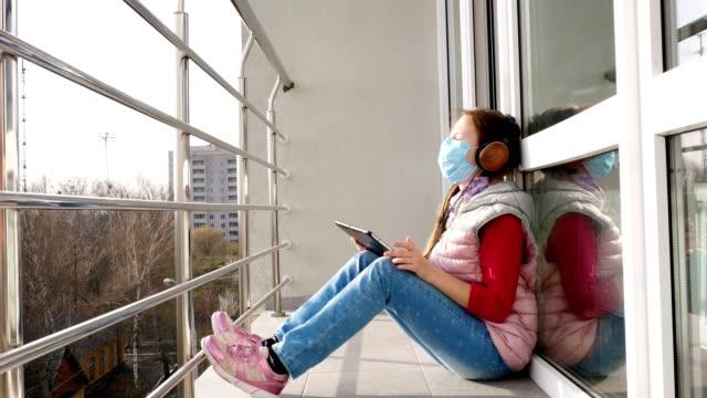 teenager-mädchen in maske und kopfhörer, musik hören auf tablet, auf offenem balkon. frühling sonniger tag. quarantäne. bleiben, zu hause studieren. coronavirus-epidemie - smartphone mit corona app stock-videos und b-roll-filmmaterial