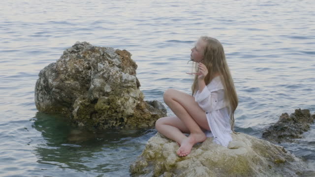 Teenager girl in white tunic sitting on rocks in sea water on summer beach. Woman photographer in bikini photographing girl teenager on sea stones in water.