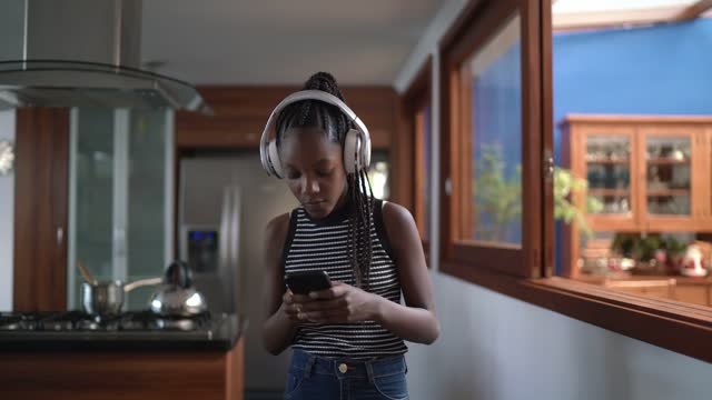 Teenager girl listening to music and walking at home