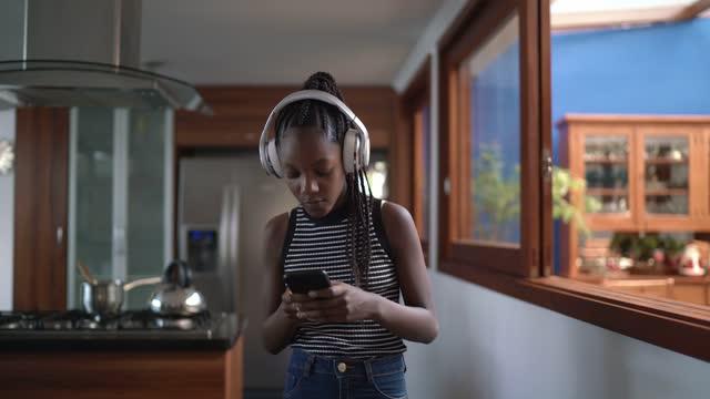 tonåring flicka lyssnar på musik och gå hemma - helgaktivitet bildbanksvideor och videomaterial från bakom kulisserna