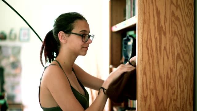 Teenager girl make order on the bookshelf in the living room video