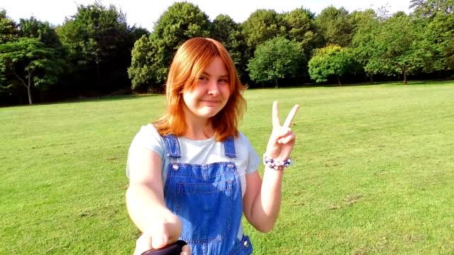 Teenager girl making selfie in park