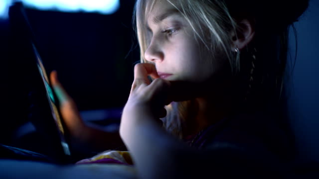 teenager girl reading from tablet at night in the bed - preadolescente video stock e b–roll