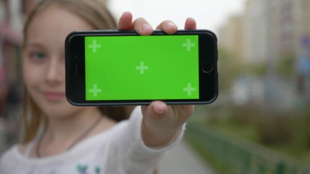 teenager girl showing mobile phone with green screen to camera on city street. close up girl teenager holding in hand front camera smartphone with green screen. copyspace for template. - mostrare video stock e b–roll
