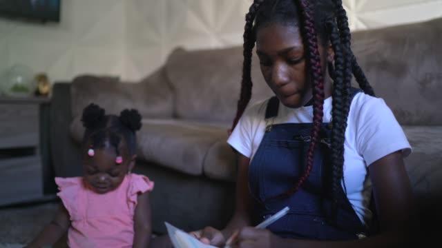 vídeos y material grabado en eventos de stock de adolescente estudiando en casa - hermana