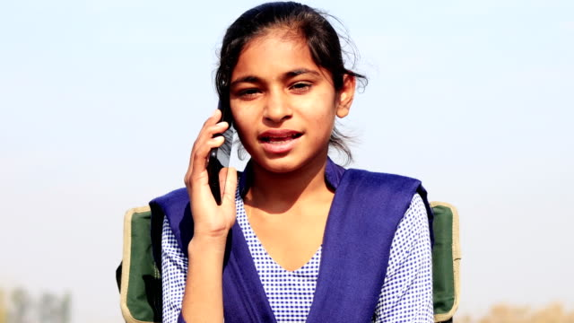 Teenager girl talking on mobile phone outdoor in nature video