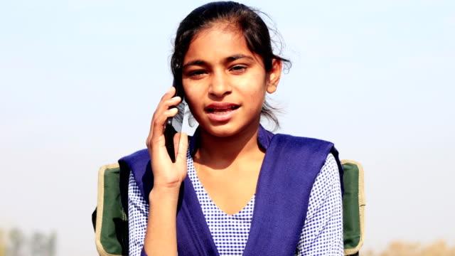 Tiener meisje praten op mobiele telefoon buiten in de natuur video
