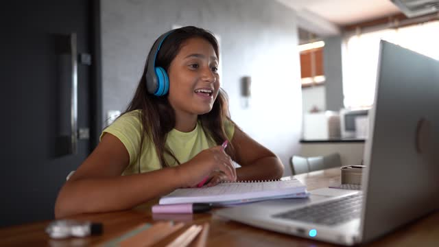 Teenager girl using laptop on homeschooling watching a online class video