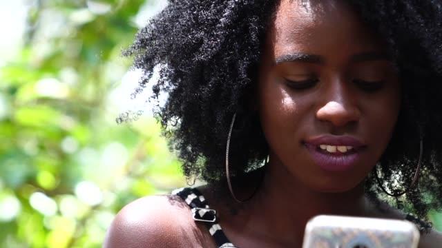 stockvideo's en b-roll-footage met tiener meisje met mobiele - afro amerikaanse etniciteit