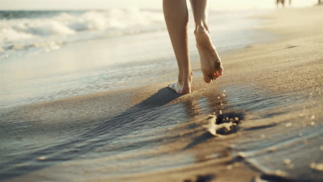 vídeos de stock e filmes b-roll de teenager girl walking on the sandy beach next to the water edge, with closeup planes of legs and footprints - sand