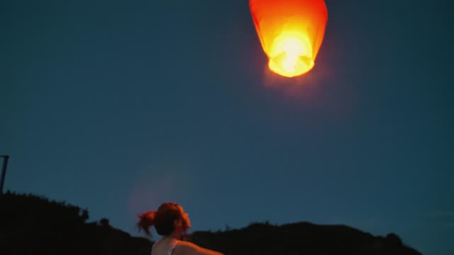 teenager girl with a chinese sky lantern making a wish. shot in slow motion - lanterna attrezzatura per illuminazione video stock e b–roll