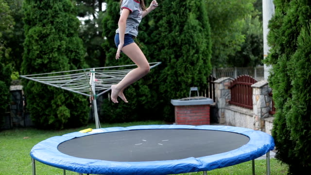 Teenager having fun - jumping on a trampoline
