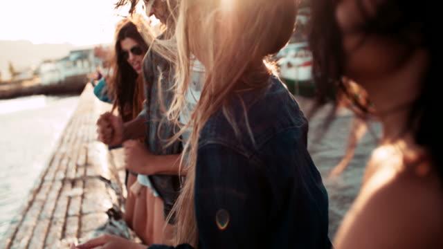 Adolescente hipster stile amici ballare sul molo al tramonto - video