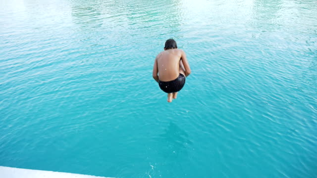 teenager jumps into swimming pool - tuffarsi video stock e b–roll