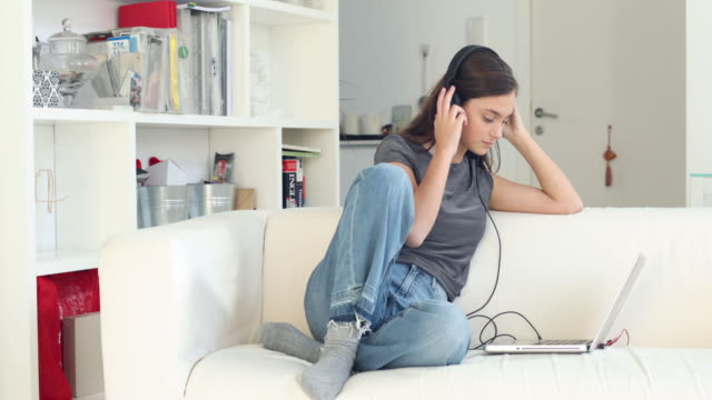 Teenager listening to online music with headphones. video