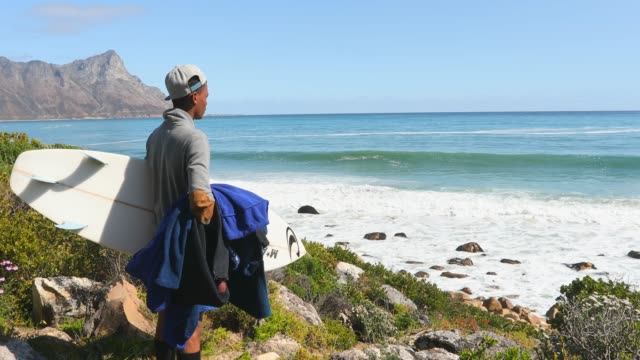 Teenager Looking at the Waves before Going For a Surf Teenage African Boy Checking the Waves before Going For a Surf western cape province stock videos & royalty-free footage