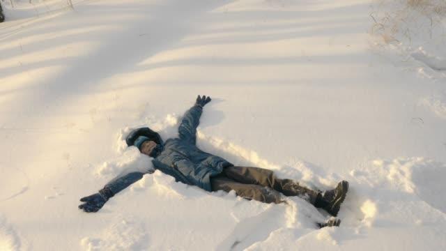 tonåring att göra snöängel liggande på snö. - snow kids bildbanksvideor och videomaterial från bakom kulisserna