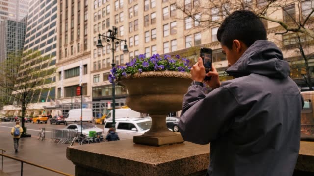 vídeos de stock e filmes b-roll de teenager male taking pictures with smartphone in new york city 4k - fotografar