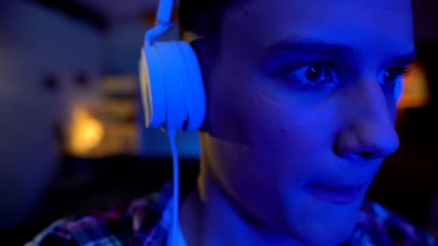 ティーンエイ ジャーにイヤホンを置くと、ビデオ ゲーム、したレジャーを再生 - ゲーム ヘッドフォン点の映像素材/bロール