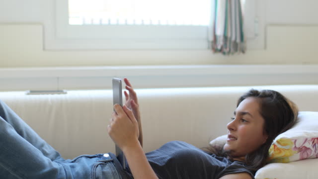 Teenager relaxing and lying down in a sofa with digital tablet. video