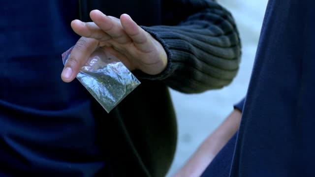 tonåringen som säljer marijuana, betalning i dollar, narkotikamissbruk bland ungdomar - kriminell bildbanksvideor och videomaterial från bakom kulisserna