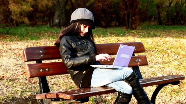 teenager sitting on bench with laptop - endast en tonårsflicka bildbanksvideor och videomaterial från bakom kulisserna