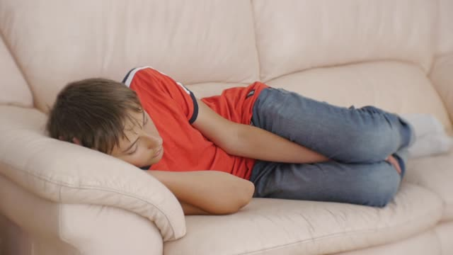 Teenager sleeping on couch. Caucasian teen boy in red t-shirt and blue jeans sleeping on beige leather sofa in daytime. Lack of sleep. video