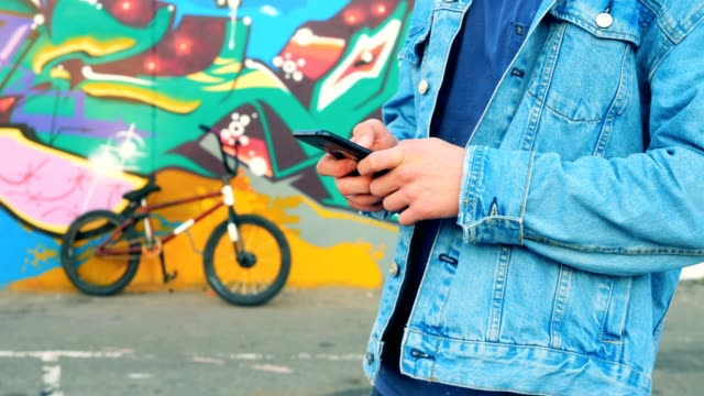 Teenager typing on a phone on a bicycle background, close up.