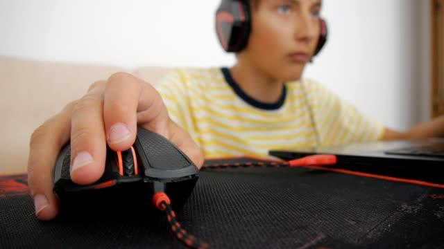 ティーンエイ ジャーは、ラップトップを使用しています。パッドの有線マウスを使用してヘッドフォンで十代。クリックし、コンピューター ゲームの黒と赤のマウスのスクロールの手のク� - ゲーム ヘッドフォン点の映像素材/bロール