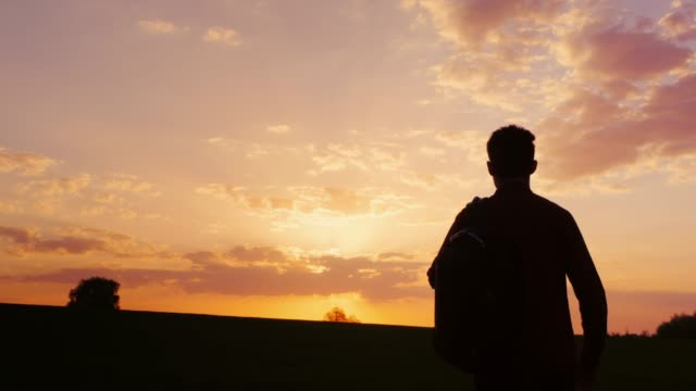 A teenager with a backpack over his shoulder goes towards the sunset in the field or in the countryside. Silhouette video, rear view. Concept - new research, forward to the unknown, to leave home