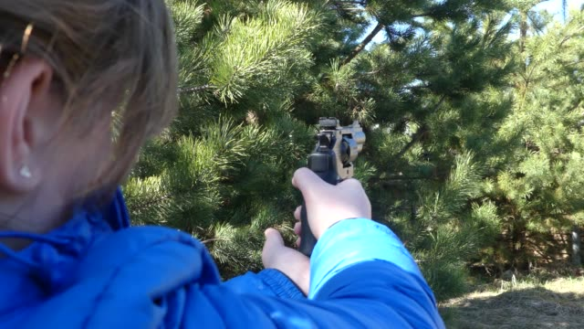 A teenager with a gun suggests a target. Teen girl shoots a pneumatic pistol. Pneumatic revolver in hand. Close-up. A teenager with a gun suggests a target. Teen girl shoots a pneumatic pistol. Pneumatic revolver in hand. Close-up. gun stock videos & royalty-free footage