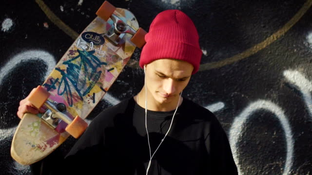 Teenager with a skateboard before graffiti wall video