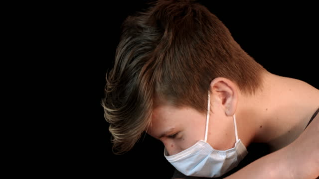Teenager with face mask coughing