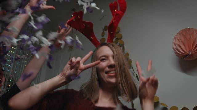 teenager with reindeer headband dancing in party - poroże filmów i materiałów b-roll
