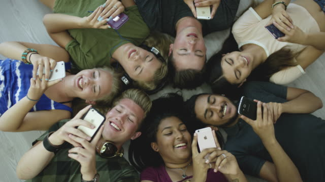 Teenagers and Technology A multi-ethnic group of teenagers are together inside using their smartphones. In this video the students are lying in a circle on the floor all using their phones and talking to each other. group of people stock videos & royalty-free footage