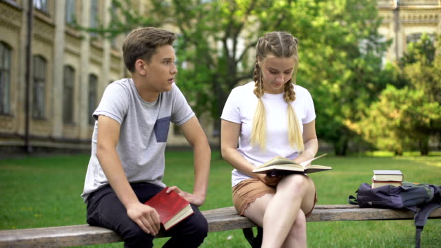 teenagers bored with studies having conversation, exhausted from reading books - compagni scuola video stock e b–roll