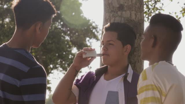stockvideo's en b-roll-footage met tieners jongens roken e-sigaret elektronische sigaret - teenager animal