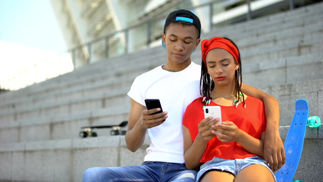 Teenagers couple spending time together scrolling social networks on smartphone