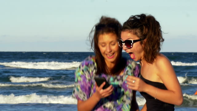 Teenagers excited when looking at a smart phone on the beach video
