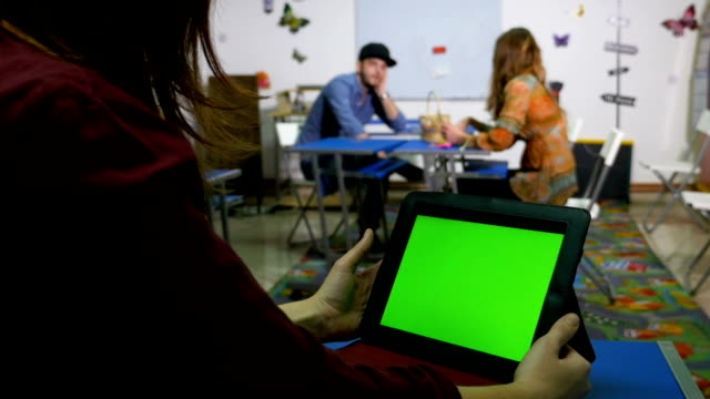 Teenagers in classroom socializing with green screen tablet pc video