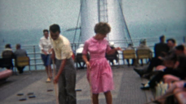 1964: Teenagers in love playing shuffleboard on a ship together. video