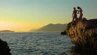 istock Teenagers jumping from a clif at sunset on the coast of Croatia and swimming back to shore, near Dubrovnik 1285715808