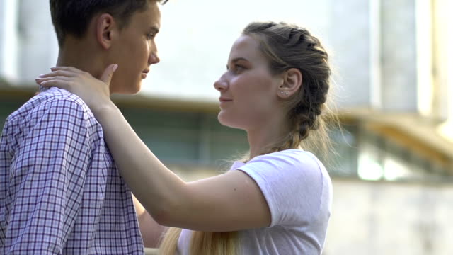teenagers kissing outdoors, hiding faces behind skateboard, shy relationship - kids kiss embarrassed video stock e b–roll