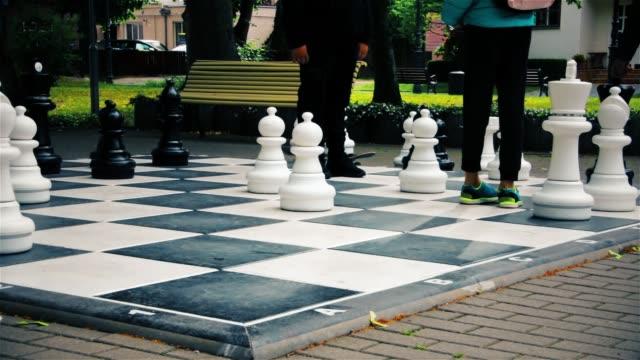 stockvideo's en b-roll-footage met tieners spelen grote straat buiten schaken - reus fictief figuur