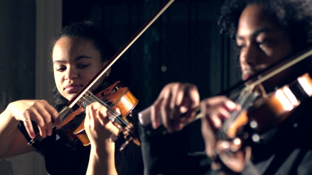 Teenagers playing violin in concert